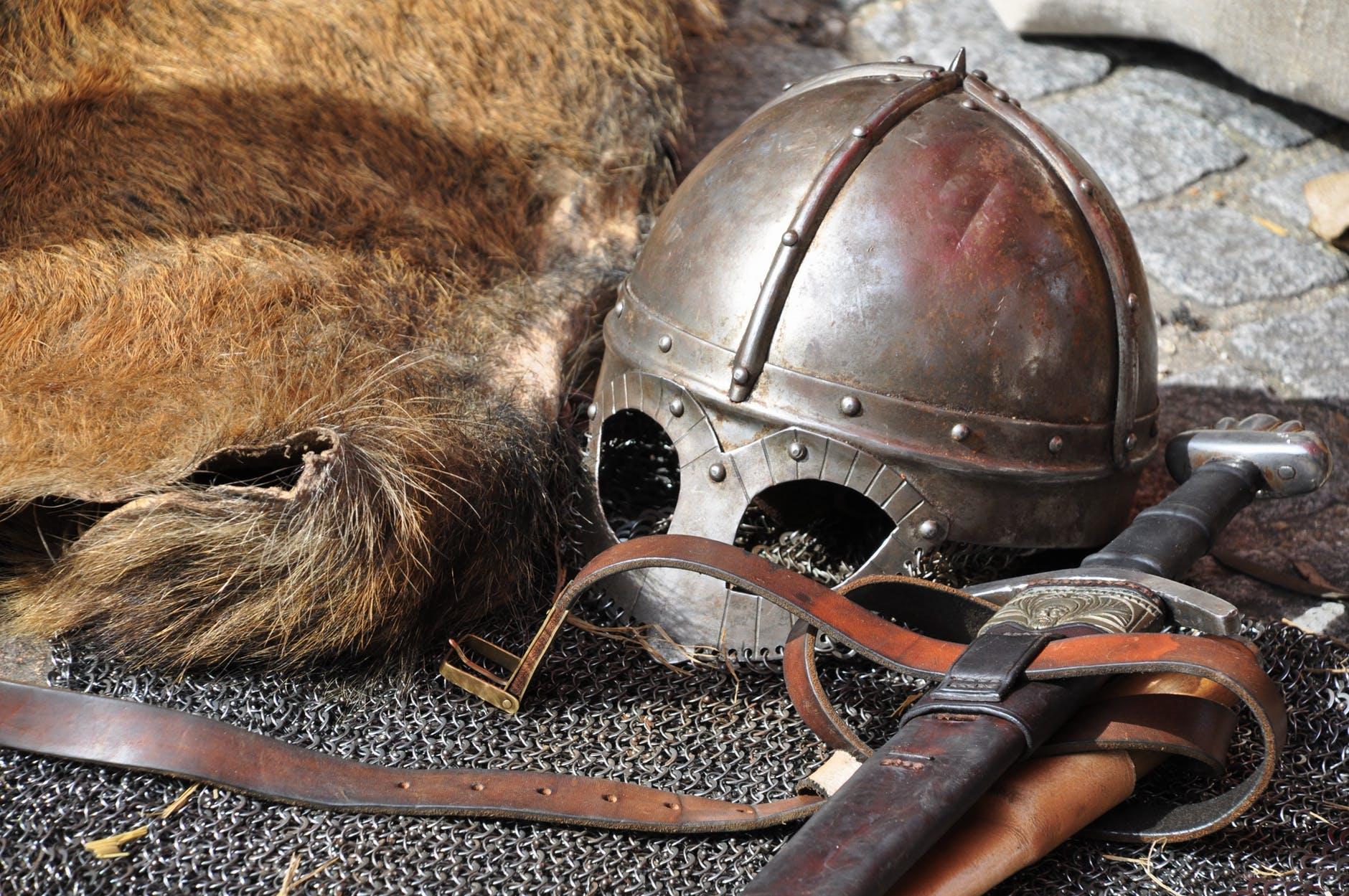 black steel helmet near black and gray handle sword
