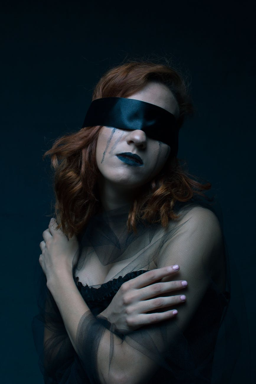 woman wearing black sweetheart neckline dress with black blindfold